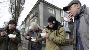 Men eat during a charity event to distribute meals for homeless people near a cathedral in Stavropol