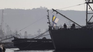 Ukrainian Navy sailors raise the Ukrainian flag on the Ukrainian navy command ship Slavutych as it is blocked by two Russian ships at the Crimean port of Sevastopol